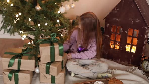 Girl Opening Presents on Christmas Morning.