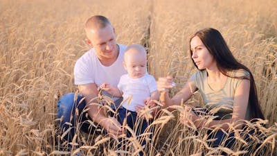 Child in Wheat Field with Parents