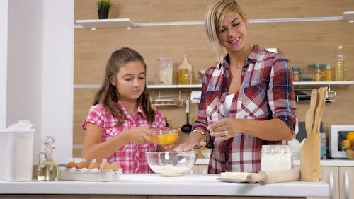Girl Pouring Eggs in Flour