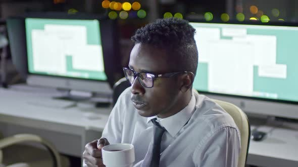 Cover Image for African Businessman Working at Night and Drinking Coffee