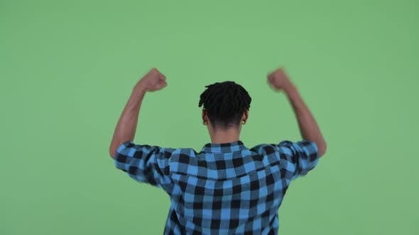 Thumbnail for Rear View of Happy Young African Hipster Man with Fists Raised