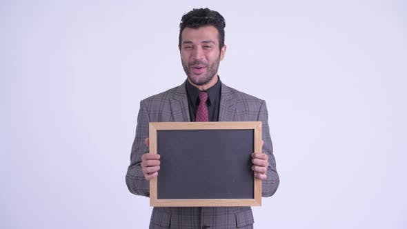 Thumbnail for Happy Bearded Persian Businessman Holding Blackboard and Looking Surprised