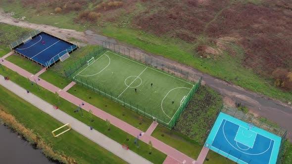 Green artificial soccer field on city quay, Football zone on promenade near river