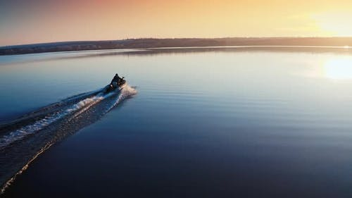 Boat on Water Surface at Sunset