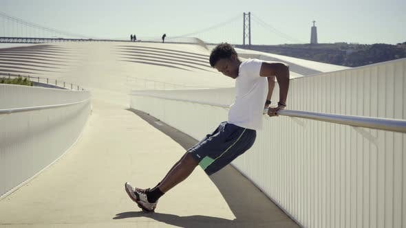 Thumbnail for Side View of Sporty Young Man Doing Push-ups Near Metal Railing