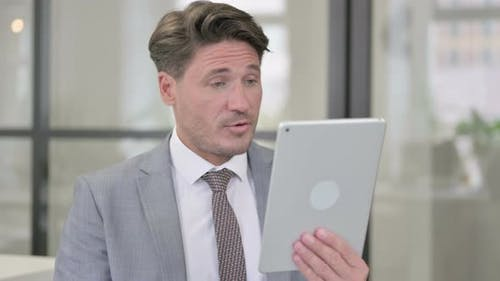 Video Call on Tablet by Middle Aged Man in Office
