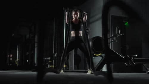 Caucasian Athletic Female Fighter Performs Exercises with Battle Ropes Endurance Training in the