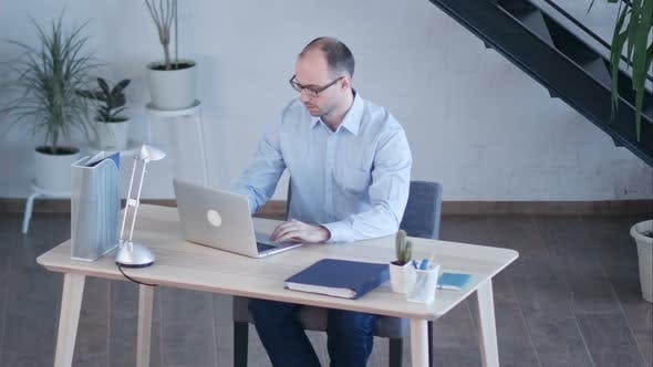 Thumbnail for Handsome Businessman Working with Laptop in Office