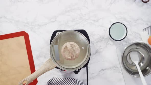 Flat lay. Step by step. Caramelizing sugar in a small cooking pot over the small electric stove