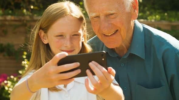 Elderly man and his Grand Daughter taking selfies