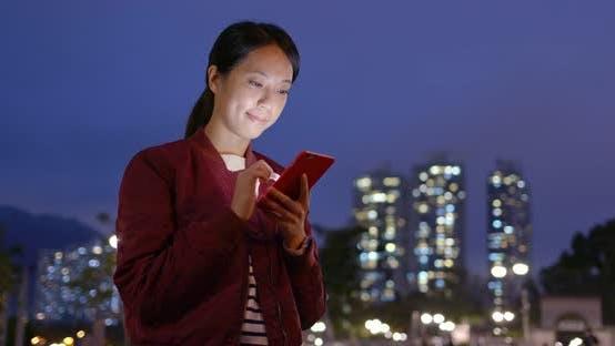 Thumbnail for Frau überprüfen auf Handy in der Stadt in der Nacht