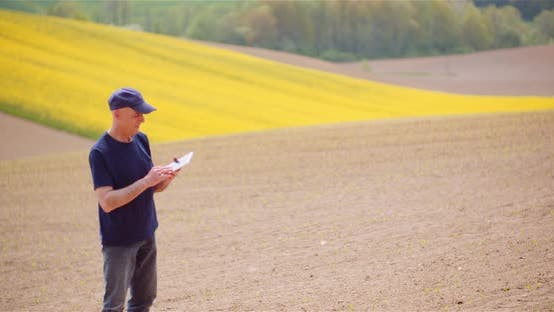 Agriculture Technology Concept - Farmer Examining Agriculture Field Working on Digital Tablet.