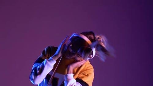 Cool Happy Teen Girl Wearing Headphones Listening Music Dancing in Purple Neon