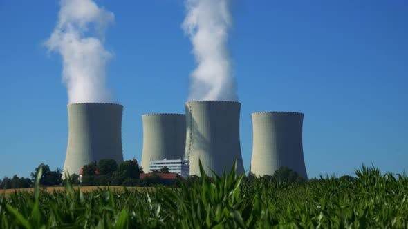 Thumbnail for Factory (Nuclear Power Station) - Buildings and Smoke From Chimney - Field with Plants and Blue Sky
