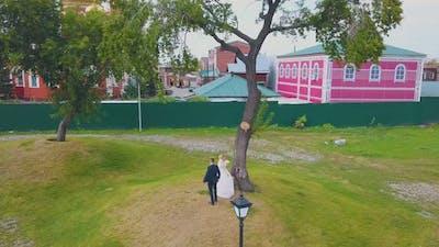 Happy Couple Dances Near Tree at Christian Church Aerial