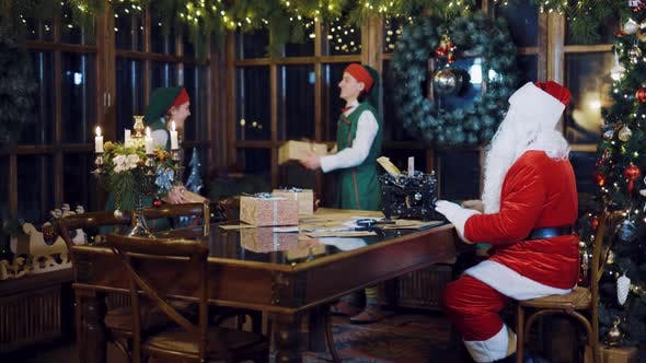 Thumbnail for Santa Claus is Writing a Letter on the Typewriter and Watching Elves