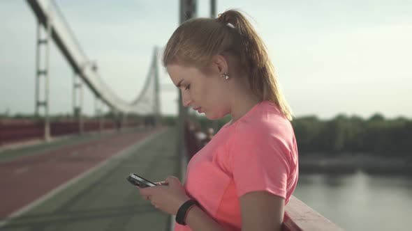 Thumbnail for Young Girl in a Sports T-shirt Writes on the Phone While Standing on the Bridge