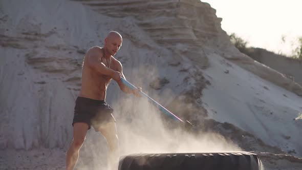 Thumbnail for Bald Man Strongman Hits a Hammer on a Huge Wheel in the Sandy Mountains in Slow Motion. Strength and