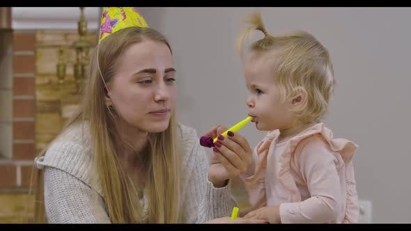 Thumbnail for Close-up Portrait of Beautiful Caucasian Woman and Little Cute Girl Playing with Party Whistles