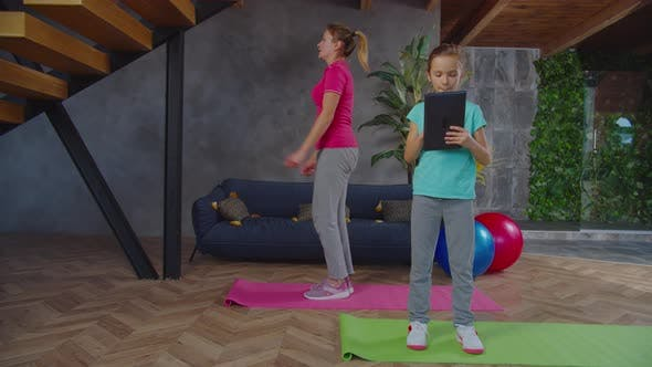 Fit Woman Exercising Under Control of Daughter
