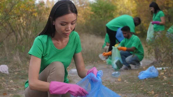 Thumbnail for Asian Woman and Other Volunteers Picking Up Trash