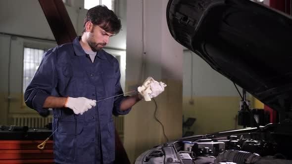 Thumbnail for Mechanic Checking Engine Oil Level in Car Workshop