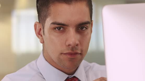 Portrait of handsome Latino business man sitting at computer looking at camera