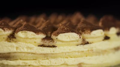 Tasty Tiramisu Cake Rotates on Black Background