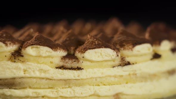 Tasty Tiramisu Cake Rotates on Black Background