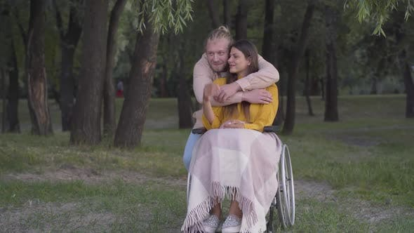 Thumbnail for Wide Shot of Handsome Loving Man Hugging Paralyzed Woman Sitting on Wheelchair in Park. Portrait of