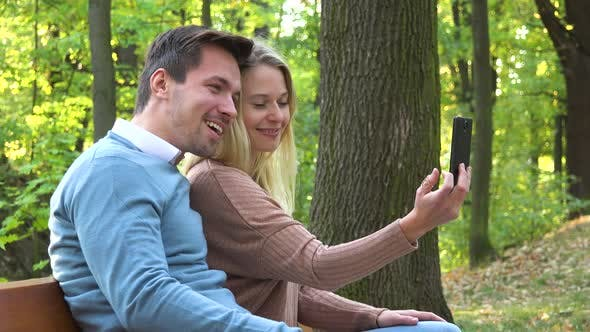 Thumbnail for A Young Attractive Couple Make a Video Call on a Smartphone in a Park on a Sunny Day