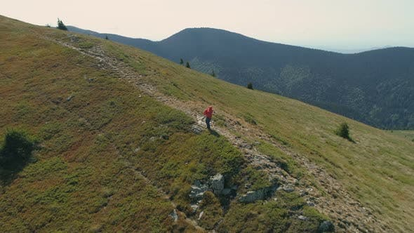 Thumbnail for Aerial View of Hiker in Red Jacket Picking Up His Bag and Continuing His Adventure