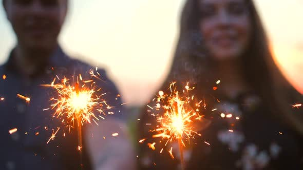 Thumbnail for The Couple Dancing with Firework Sticks on an Evening Sunset.
