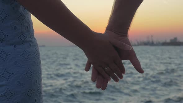 Thumbnail for Close-up Shot of Romantic Couple Holding Hands on the Beach Against Sunset Piraeus, Greece