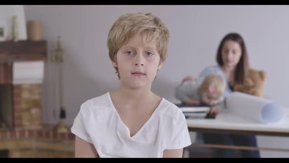 Thumbnail for Porträt von blond kaukasischen junge mit grauen Augen Blick auf Kamera als seine Schwester und Mutter spielen