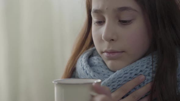 Thumbnail for Portrait of Teenage Girl Wrapped in Warm Scarf Holding a Cup of Hot Tea in Hands. The Girl Feels Bad