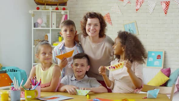 Thumbnail for Happy Female Teacher and Multiethnic Children Posing with Origami Boats