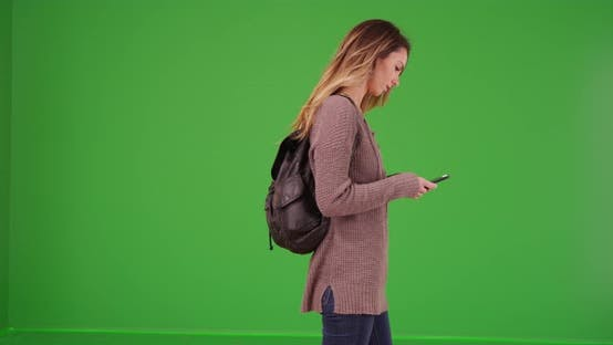 Thumbnail for White female millennial texting on smartphone on green screen