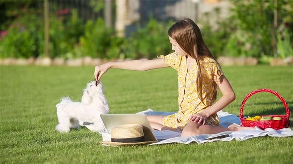 Little Smiling Girl Playing with Puppy in the Park