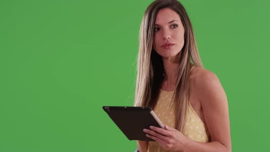 Thumbnail for Happy millennial white woman using tablet computer on greenscreen