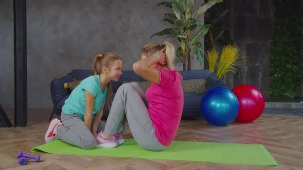 Active Fit Mom Doing Sit Ups with Help of Daughter