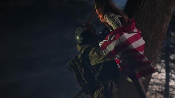 Un soldat de retour au pays s'étreignant avec sa fille et son drapeau américain au Ralenti