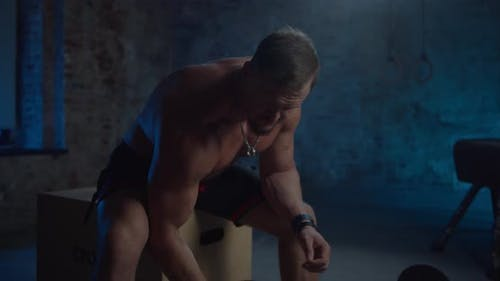 Handsome Fitness Man Shirtless Bodybuilder Trains Biceps with Dumbbell in Hands in Sports Club or