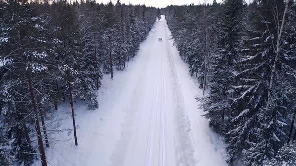 Aerial view of a car driving in the snowy forest in Estonia.
