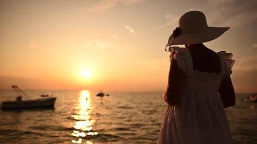 Elegant Retired Woman in White Dress Enjoying Retirement in Front of the Sea
