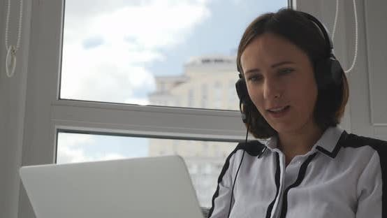 Female support manager in headphones cunsulting customers on laptop and chating online