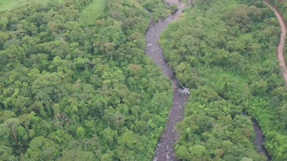 River through rainforest at Arenal Volcano National Park, Costa Rica. High aerial drone view