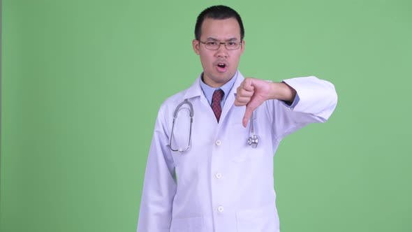 Cover Image for Angry Asian Man Doctor with Eyeglasses Giving Thumbs Down