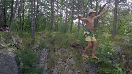 Thumbnail for A man tries to balance while slacklining on a tightrope.