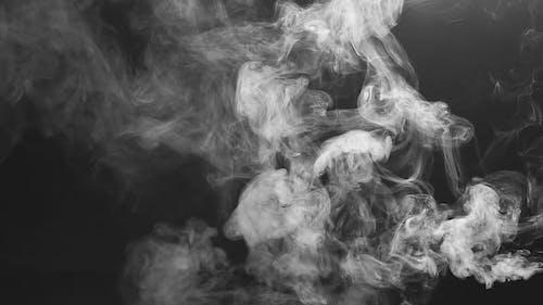 Vape Concept. Smoke Clouds and Vape Liquid on Dark Background
